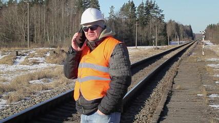 Railway employee talking on the cell phone on railway