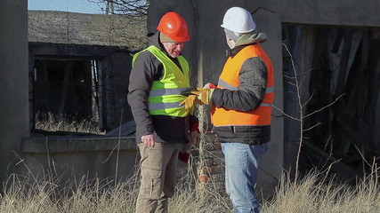 Construction engineer with tablet PC near destroyed building