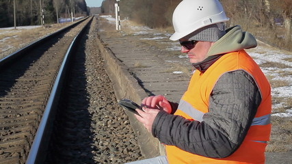 Railway employee with tablet PC near the railway