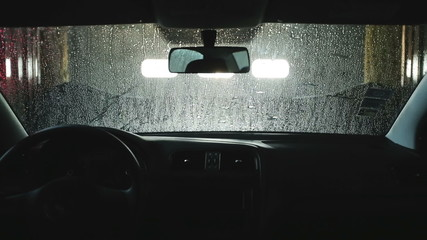 Automatic car wash. Roller soaping and scrubbing the windshield