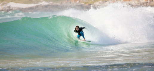 Surfer surfing in tunnel of large wave
