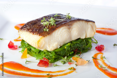 a piece of fried fish on white plate - 78401688