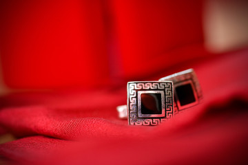 Black cufflinks for shirt in a nice red background