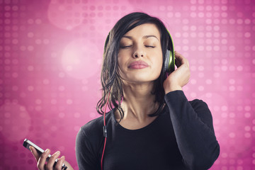 Happy calm girl enjoying listening to music with earphones.