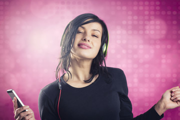 Smiling girl listening to music with earphones and dancing.