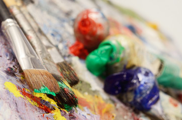 Artistic palette with colourful oil paints, dirty brushes
