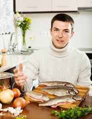 Handsome man cooking trout fish