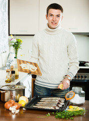 Handsome guy cooking  fish with lemon and onion