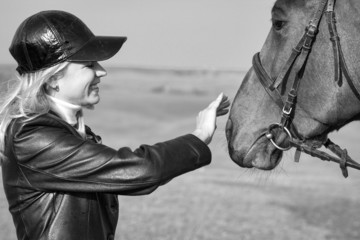 Horsewoman stroking the horse's head, Black and White