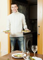 Smiling man serving cooked fish on  table