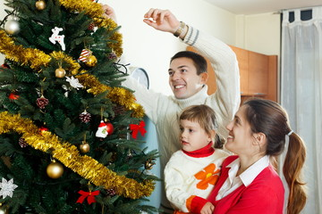 Parents and  girl decorating Christmas tree