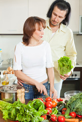 A man and a young woman with vegetables in the kitchen
