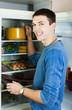 Man putting pan into refrigerator