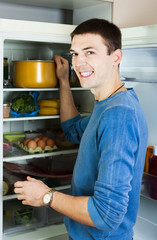 Man putting pan into refrigerator