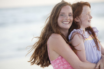 Portrait of mother and daughter embracing on sunny beach