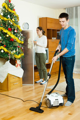 Smiling couple doing housework