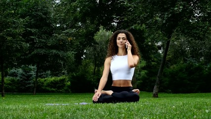 Young woman yoga in the park talking on a phone