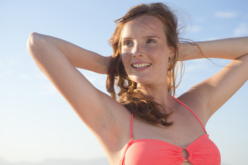 Smiling woman, with arms raised behind head, on sunny beach