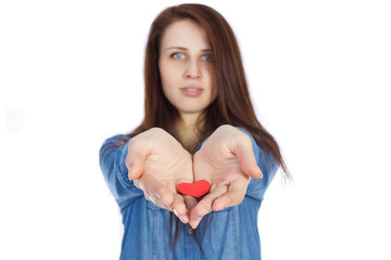 Beautiful brunette holding a red heart on white background