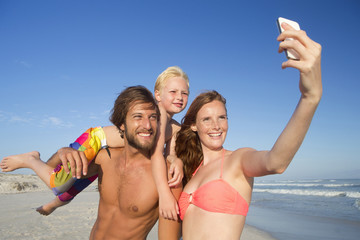 Portrait of happy couple with son on shoulder, taking selfie on sunny beach