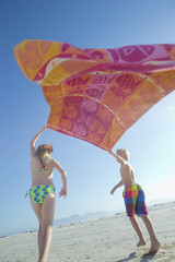 Young boy and girl holding towel above head on sunny beach