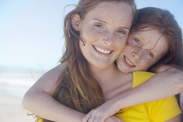 Portrait of smiling girl, embracing mother, on sunny beach