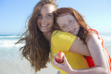 Portrait of smiling girl holding apple, embracing mother, on sunny beach