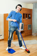 Smiling young man cleaning living room