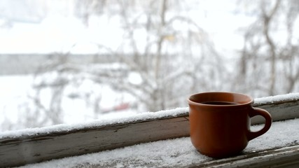Cup of coffee on old window sill on background of falling snow