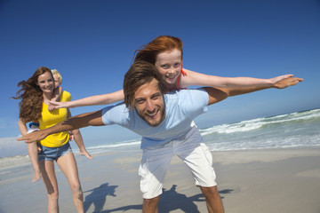 Mother and father, giving two children piggy back, on sunny beach