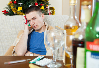 young hungover guy sitting by table with bottles and pills