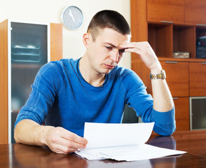 Upset guy reading document at home