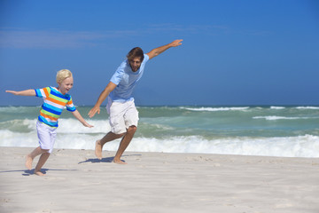 Smiling Father and son, pretending to fly, running on sunny beach