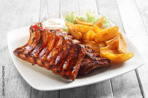 Leinwandbild Motiv Mouth Watering Grilled Pork Rib and Fried Potatoes