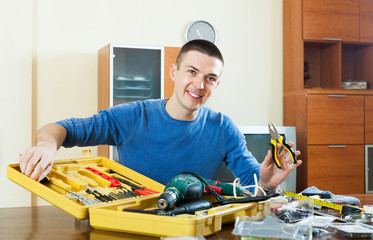 Happy smiling man with tool box and pliers