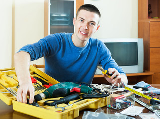 Happy guy with  tools in toolbox at home