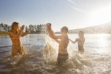 Happy family having water fight in lake