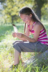 Smiling girl, looking at feather, sitting in treelined field