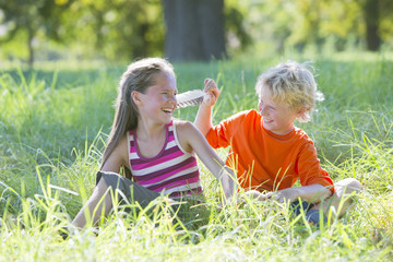 Young boy tickling young girl with feather, sitting in treelined field