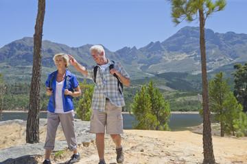 Senior couple hiking on mountain path next to lake
