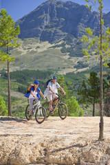 Senior couple mountain biking on mountain path