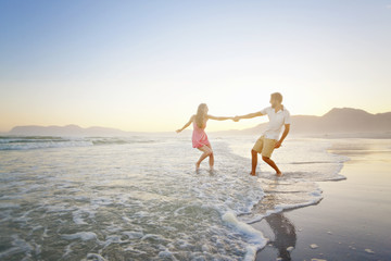 Couple, holding hands, playfully walking through waves on sunny beach