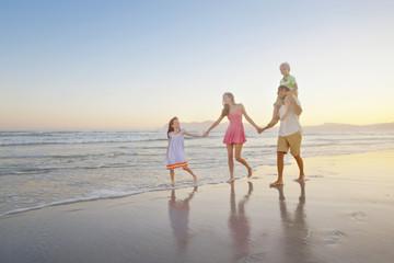 Happy family walking, holding hands on sunny beach