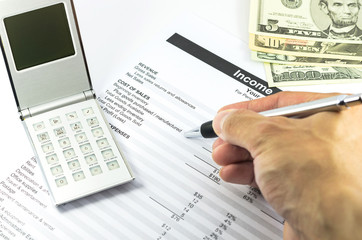 mark on income statement report with calculator and pen