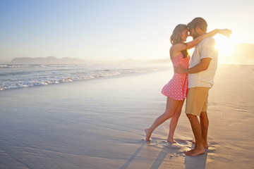 Romantic couple embracing, about to kiss, on sunny beach
