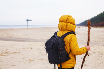Man in yellow jacket stands on the beach.