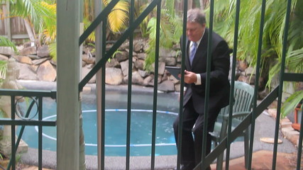 Businessman leaves by a pool through the bars of fence