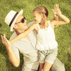 portrait a father and daughter sitting on the grass at the day t