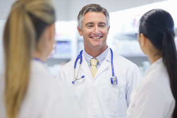 Doctor, wearing stethoscope, smiling at colleagues