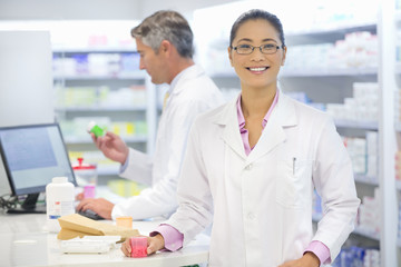 Pharmacist, holding medication pot standing at pharmacy counter